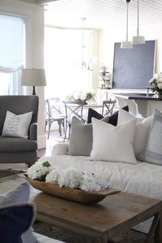 Beautiful white living room with rustic farmhouse style and a chalkboard in the dining room.