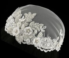 This gorgeous bridal cap has much detail! Soft ivory bridal illusion is edged by lace and accented with chiffon flowers, ivory pearls and rhinestones. The centerpiece to the design is a leaf pattern covered in silver lined bugle beads and rhinestones. Any Boho bride would be happy with this piece!