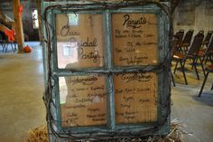 An old window frame, painted and distressed. instead of wedding programs, the bridal party is written on the glass panes using a black sharpie. A piece of burlap was stapled to the back to give it an additional rustic touch.