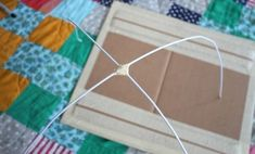 Shape the  hangers into an arch, tape the middle together, and stick one end through each hole. Secure with tape.
