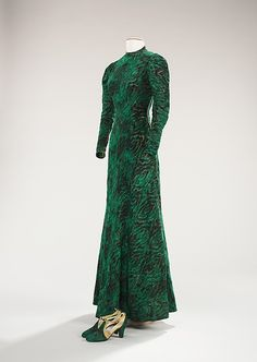 Evening Ensemble by ES, 1933-35. The many layers and shades of green in the print, produces depth and the metallic threads woven throughout lend a luminous quality, making the overall effect like sunlight shining over a mysterious forest. Millicent Rogers, the original owner of this dress, gave her entire wardrobe to the Brooklyn Museum, and throughout the almost 200 examples of Schiaparelli's work from Rogers' collection, this ensemble best illustrates Schiaparelli's love of unique fabrics.