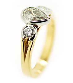 18ct Yellow & White Gold Diamond Ring      Rubover set pear shaped diamond flanked by two round brilliant diamonds 3/4 rubover set in white gold on a yellow gold split shoulder half round shank.