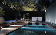Love the black wall and how it frames the illuminated trees beyond, also providing a focal point for the Buddha statue atop of the water.