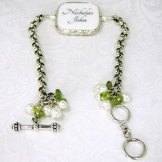 A Rolo chain bracelet with luscious pearls and Peridot dangles. It holds a custom framed photo tile with images baked in clay, and sealed to a glossy, waterproof finish.