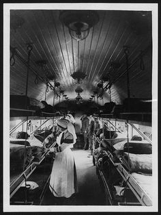 Interior of a ward on a British Ambulance Train in France    Interior of an ambulance-train ward, France, during World War I. This image is very striking due to the lighting and the tunnel effect of the train carriage, which is emphasised by the parallel lines of the wooden panelling on the roof. Two nurses are busy tending the wounded while two officers survey the scene from the top of the carriage.    Ambulance trains were used in the main to transport large groups of soldiers to the…