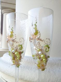 Beautiful pair of two beach wedding champagne flutes are hand painted with an original design. Hand decorated with real starfish, sea shells, sea glass and pearls. Colors are lime, champagne and ivory.    Its a perfect addition to your wedding reception, or a wonderful bridal shower gift! High 8.5    Custom champagne glasses may be created to fit your needs. Names and date may be painted to customize to your occasion. Customizations are included in the price.    Glasses will be carefully…