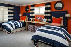 Vibrant Orange Accent Wall and Thick Navy and White Striped Linens in Boy's Bedroom With Pair of Twin Beds