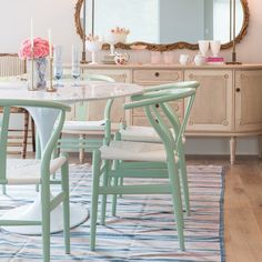 A dining room with mint green pastel chairs and a pink and blue pastel rug.