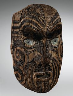 Maori Mask, New Zealand. Sotheby's | Maori head, the back of which bears an old inscription which, together with the carving style, indicates that it once adorned a piece of architecture. | In this male figure the artist has used an Arawa realistic tattooed face mask.