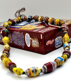 This handmade paper bead necklace is made from multiple cereal box cardboard, including Frosted Mini-Wheats, Golden Grahams, and Cheerios, and