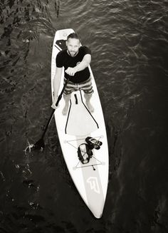 Man Standing on Surfboard on Water Rowing in Greyscale Photography  Free Stock Photo