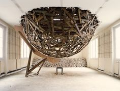 Sambre's Disco Ball. After selecting two rooms as his workspace on the third and fourth floors, he drilled a large hole between them and suspended a massive sphere made of ripped-up parquet floorboards. The low wall backdrop is made of plaster and rubble recuperated from the process