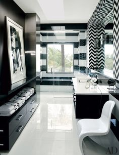 An Andy Warhol silkscreen of Mick Jagger is featured in Tommy's bath. The sink is by Kallista, the wall at right is clad in a Martyn Lawrence Bullard for Schumacher wall covering, and the floor is paved with glass tile by WalkOn Tile   archdigest.com
