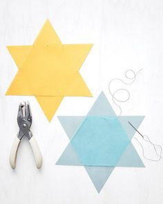 Colored paper, a hole punch, and needle and thread are all you need for gorgeous DIY Hanukkah window stars.