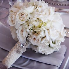 White tea rose bouquet with pearl seed embroidered lace wrap and antique brooch. Muted periwinkle satin table linens. So beautiful!!
