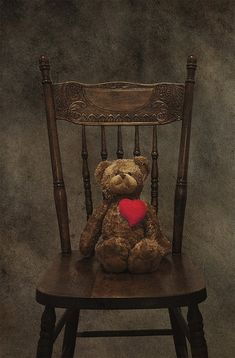 A beautiful chair with a brown Teddy Bear and a red heart. Lovely photograph.