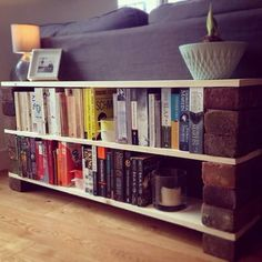 Shelf to hide back of sofa in open plan lounge. Bricks + planks = £30 bookshelf!