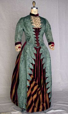 Late 1880s sage green brocade Visiting Dress. 2-piece, silk faille w/silk floral design, metallic embroidered cream lace and burgundy velvet bodice trim, skirt w/striped panels of burgundy ribbed velvet and gold silk, and forest green skirt lining w/built-in bustle.
