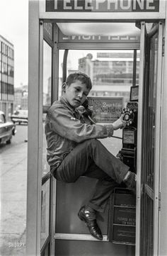"""Boy in telephone booth, Boston, 1963."""