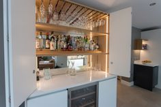 A bespoke Drinks Cabinet with antiqued mirrored glass and solid oak glass holders. The flat slab doors with bi-fold opening are designed to match the handleless kitchen. Handleless Kitchen, White Kitchen Cabinets, Drinks Cabinet, Liquor Cabinet, Slab Doors, Glass Holders, Dining Room Design, Kitchen Furniture, Solid Oak
