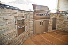 Gorgeous Outdoor Kitchen with a stacked stone facade appearance! Completed with stainless steel appliances, lighting, covered patio, and landscaping.