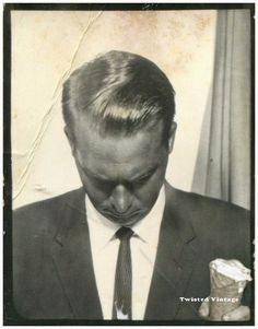 Odd vintage photo booth, man holding ice cream cone, looking down.