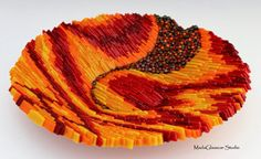 This heavy, sturdy glass bowl is constructed using the on edge method of fusing glass. Made of reds, oranges and yellow art glass with millefiori glass accents. 15 wide x 3 high Food safe Hand wash