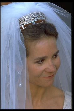 Infanta Elena wore the Marichalar diamond tiara, a neo-classical tiara with a laurel wreath topped by Greek keys, which was a gift from the groom's family