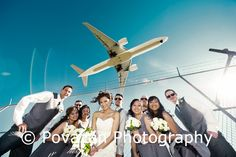 Vancouver airport wedding party formals with bride and groom and plane flying above them. Unique, edgy, fun wedding photographers from north vancouver - Povazan Photography.