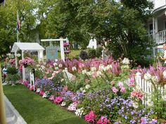 Mackinac Island.   So Pretty!   Fence, Arbor and all those flowers!