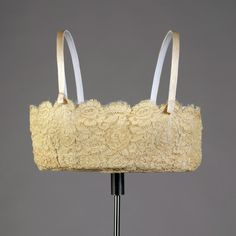 Brassiere, American, ca. 1925. Ecru colored machine lace bandeau; straps of silk ribbon. Gift of J.B. Britton in memory of Katherine Lynch Bates, KSUM 1985.4.17
