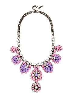 Two perfectly paired shades of bright neon adorn this fantastically floral statement piece, with plenty of dangling elements and sparkling crystals to add movement and drama.
