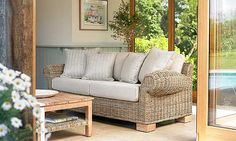 A contemporary conservatory or garden room sofa, woven from robust rattan in Kubu Grey. It would be very suitable for a family room. There is a matching armchair and a large choice of fabrics in different price bands. Choose scatters in different fabrics for colour and interest. The Kubu grey occasional tables come with either distressed wooden tops to match the chunky sofa feet, or there is a low square table with a glass top.    £980 three-seater sofa in Victoria Cream