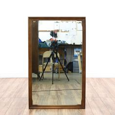 This mirror is featured in a solid wood with a glossy walnut finish. This mid-century modern style accent mirror has a rectangular beveled frame. Beautifully minimalist piece that's perfect for the mantelpiece, entryway, or vanity wall! #midcenturymodern #decor #mirror #sandiegovintage #vintagefurniture