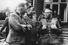 From left to right: Richard Baer (commandant of Auschwitz), Karl Hoecker (his adjutant), and Rudolf Hoess (the former commandant) chat on the grounds of the SS retreat, Solahuette, outside of Auschwitz. Photo USHMM.