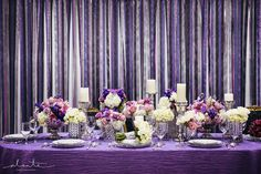 Purple wedding table decor. Purple tablescape. Purple and silver centerpieces. Purple table linen. Purple flowers. Silver chargers. Wedding China. Wedding reception decor.