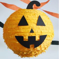 Pumpkin Piñata | Martha Stewart Living - Finish the piñata by stringing twine through the lantern's hooks. Glue a black cardstock stem to the top of the lantern; if desired, also add a plastic spider and a black tassel to the pull strings for visual appeal. #Sponsored by Hershey's