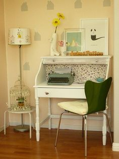 A White Desk Is Positioned Against Pastel Yellow Walls In This Small Office Area Green Electric Typewriter Complements The Chair And Artwork