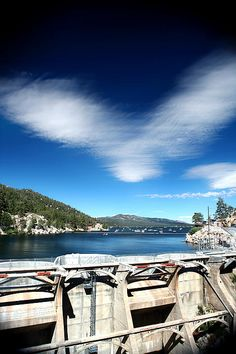 The Dam at Big Bear Lake (Vertical) - A beautiful photo of the concrete Dam at Big Bear Lake California with a clear blue sky, fluffy white clouds, and boats on the calm reflective water.