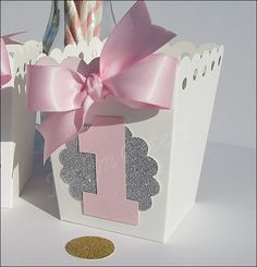 She's turning one! Our handmade baby girls pink and glitter number one popcorn favor box features the number one and a luxury satin hand tied bow. Fill with goo