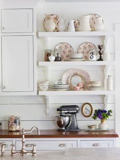 "Shelves for Storage and Display ""Open shelves and white cabinetry keep the look open and airy in this (small) cottage kitchen. Vintage dishware and floral-pattern china create a pretty display that not only looks great but also remains within reach of the kitchen's main prep zone."""
