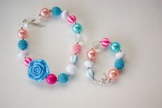 A Blue, White & Pink Chunky Bubble Gum Necklace and bracelet set. Has large chunky beads and a rose. Sized for a Toddler/Child Perfect for dress up or photoshoots.  Looking for a matching Headband or