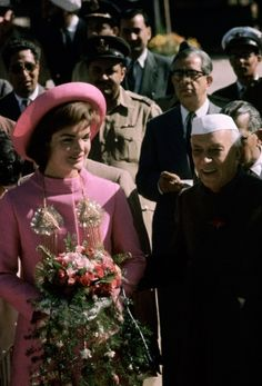 Donning a vibrant pink, rajah-inspired coat by Oleg Cassini and a matching Halston hat, First Lady Jacqueline Kennedy is heartily welcomed b...