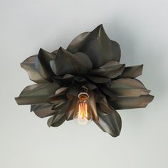 Vintage Magnolia Blossom Semi Flush Ceiling Light.  An industrial look with a soft flower blossom design.  Crinkled gun metal give this fixture a unique look and the Edison bulb changes the look.  Bronze and rust.