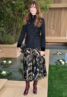 Caroline de Maigret wears a band-style jacket, printed midi skirt, embellished Chanel bag, and burgundy boots