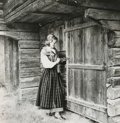 Swedish girl in a Delsbo dress by a log house, Sweden.