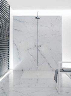 All-white marble bathroom with Tara-series Dornbracht shower.