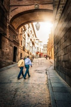 Two men crossing street of Toledo, Spain. Old wooden building with stone wall. Beautiful spanish architecture. Streetlight hanging from arch. Bright sunshine. Popular tourist place in Europe. Stock Photo