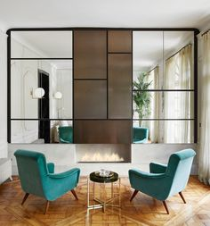 A Mondrian-inspired mirrored wall custom designed by Laura Gonzalez features central panels in bronze metal above a concrete fireplace base. | archdigest.com