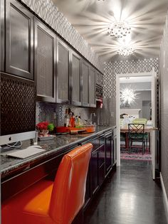 Graciela Rutkowski Interiors  Stunning galley butler's pantry with Robert Abbey Anemone Ceiling Lights, gray ceiling, Kelly Wearstler Imperial Trellis Wallpaper, glossy black cabinets, black granite countertops and orange leather chair.